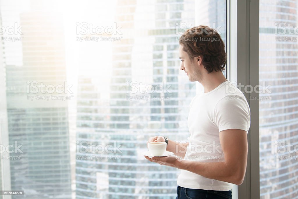 Young handsome man near full length window stock photo