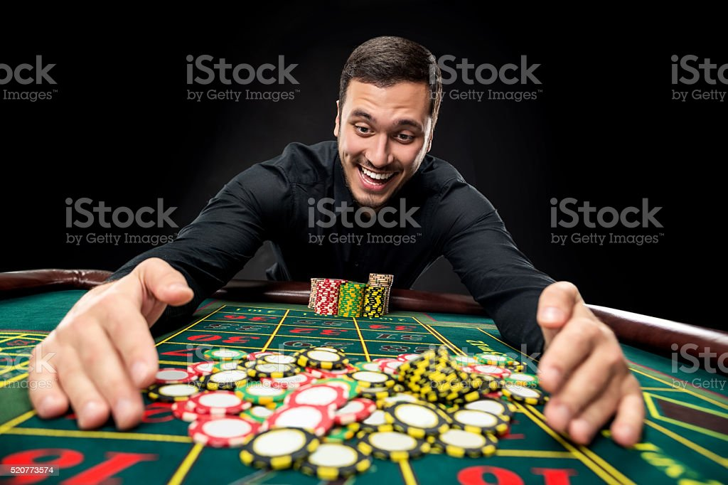 Young handsome man playing roulette wins at the casino stock photo