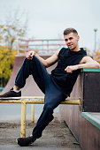 Young handsome man resting on a skateboard park ramp.