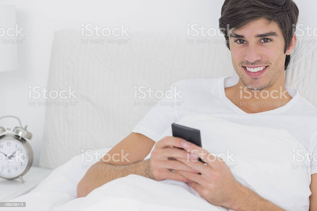 Young handsome man sitting in bed using smartphone royalty-free stock photo