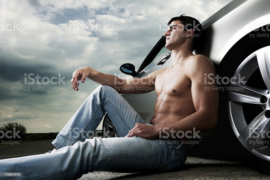 Young handsome man sitting next to his car. royalty-free stock photo