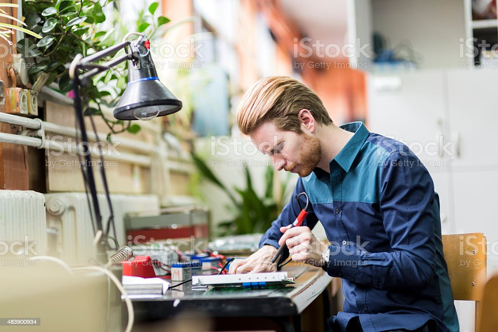 Young handsome man soldering a circuit board stock photo