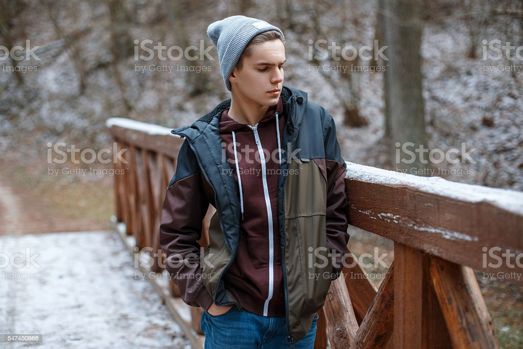 Young handsome man stands on a wooden bridge stock photo