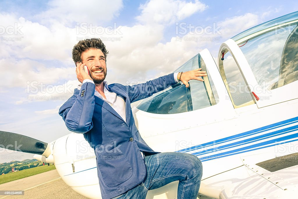 Young handsome man talking with mobile smart phone at airplane stock photo