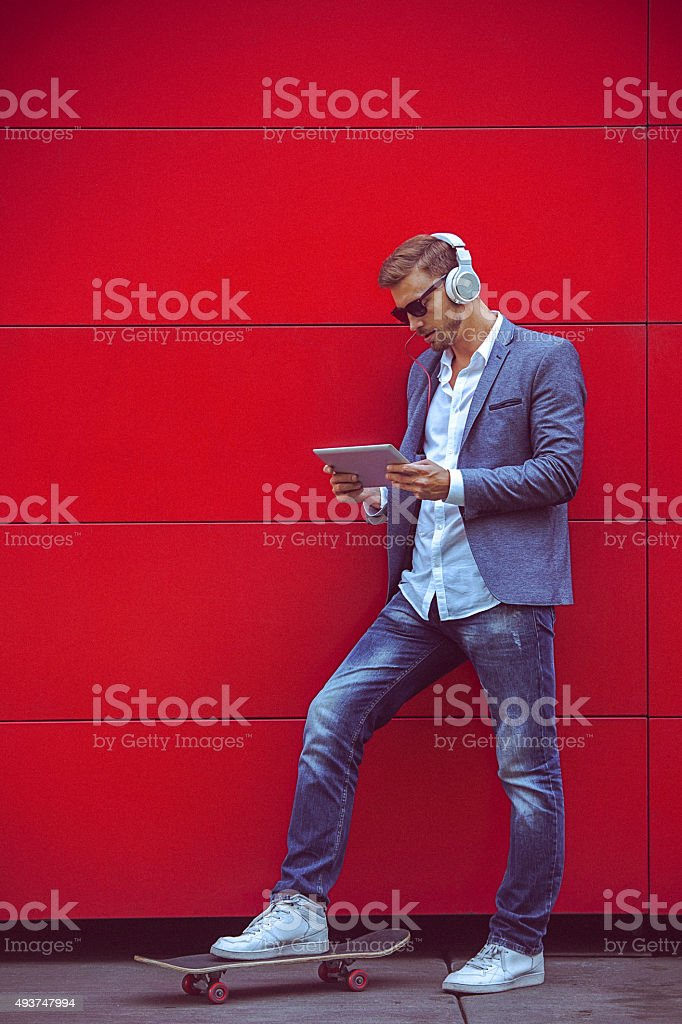 Young handsome man using digital tablet beside the red wall stock photo