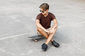 Young handsome man with hairstyle in sunglasses sits on  skateboard.