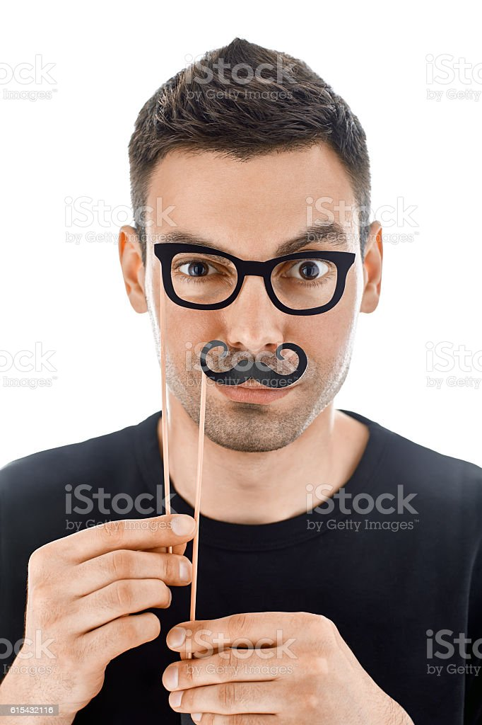 Young handsome man with paper moustaches and glasses making face stock photo