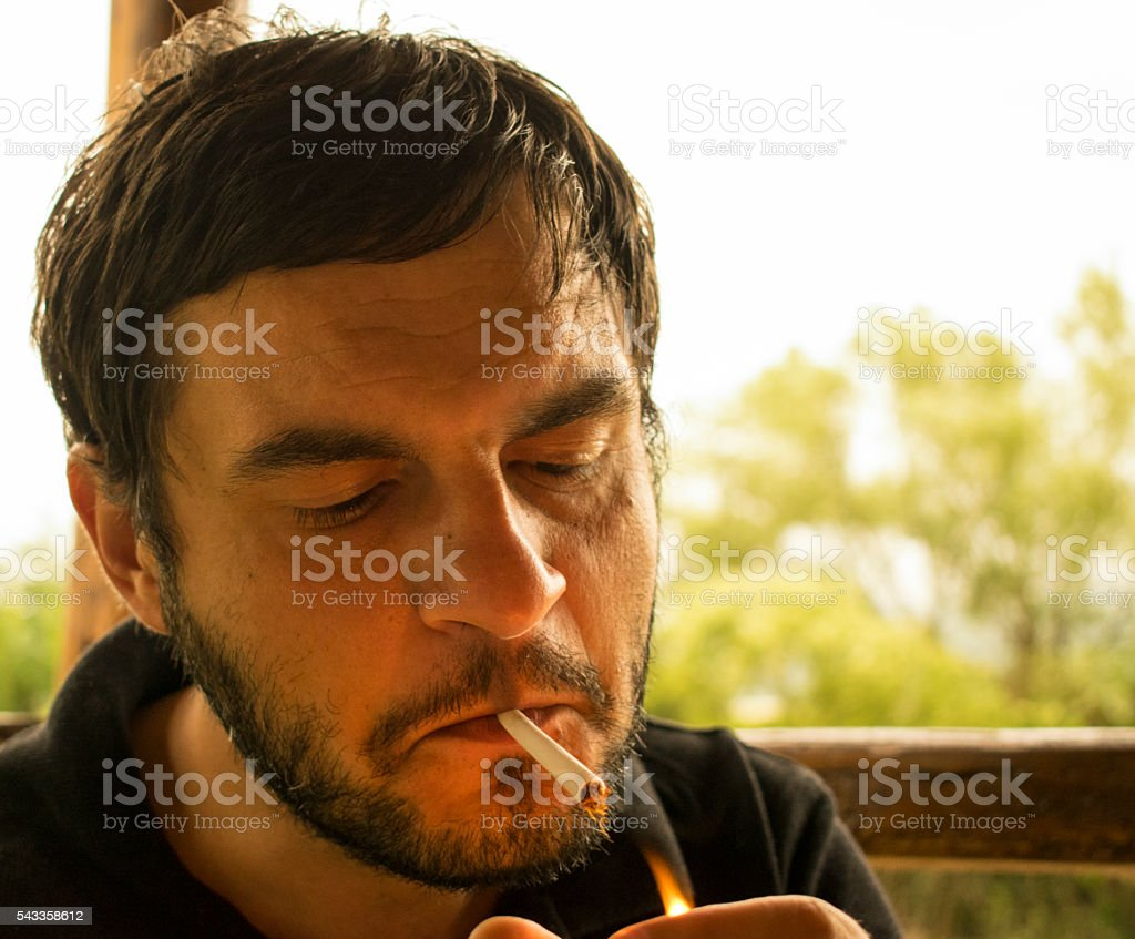Young handsome man with the beard lighting a cigarette stock photo