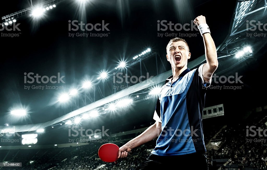 Young handsome sportsman celebrating flawless victory in table tennis stock photo