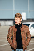 Young handsome stylish man in brown jacket in autumn time