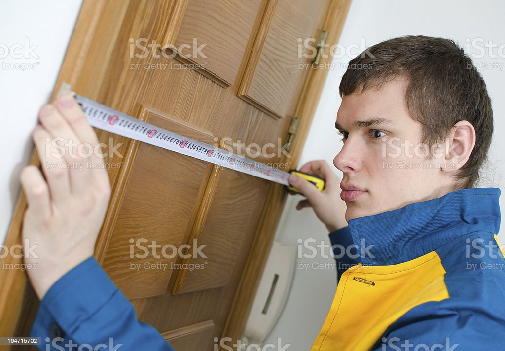 Young handyman in uniform working with measure tape royalty-free stock photo