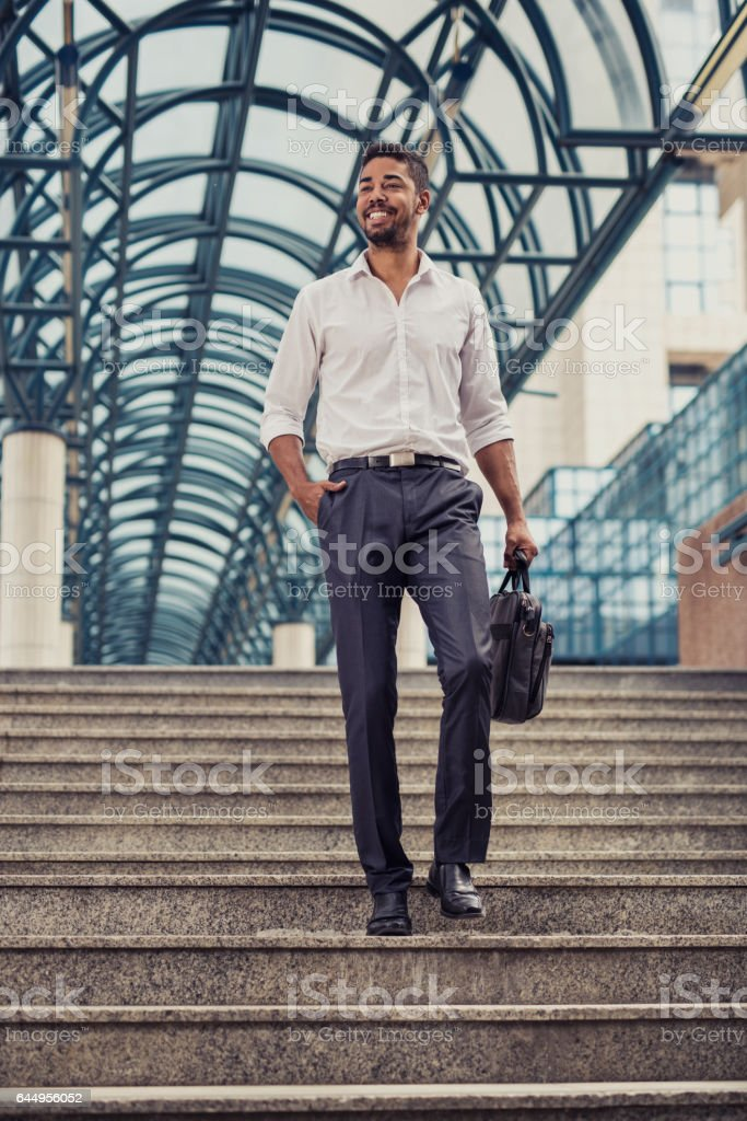Young happy African American businessman moving down the stairs. stock photo
