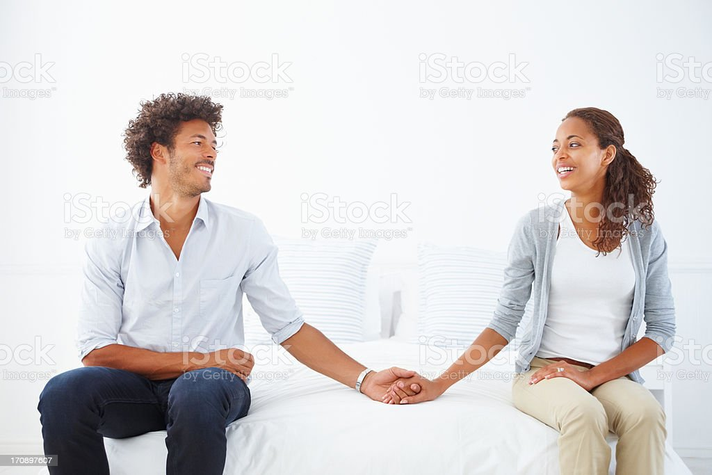 Young happy African American couple sitting on the bed holding hands together stock photo