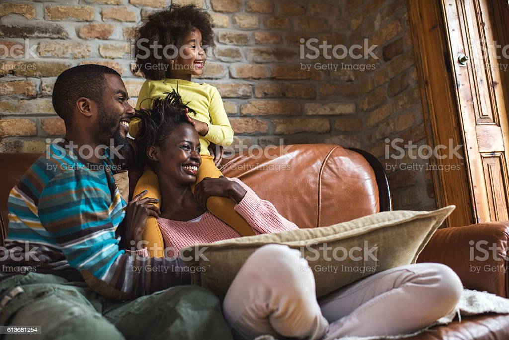 Young happy African American family relaxing on sofa at home. stock photo