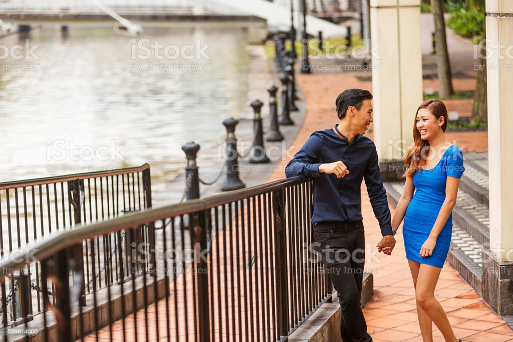 Young Happy Asian Couple Walking Together by the Singapore River stock photo