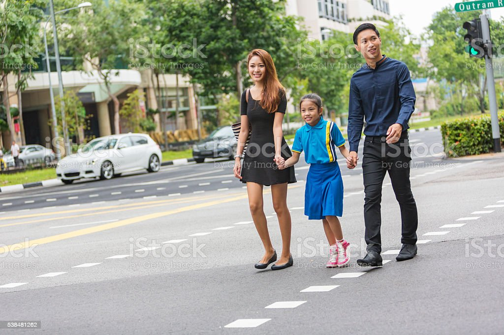 Young Happy Asian Family Crossing the Road Together in Singapore stock photo