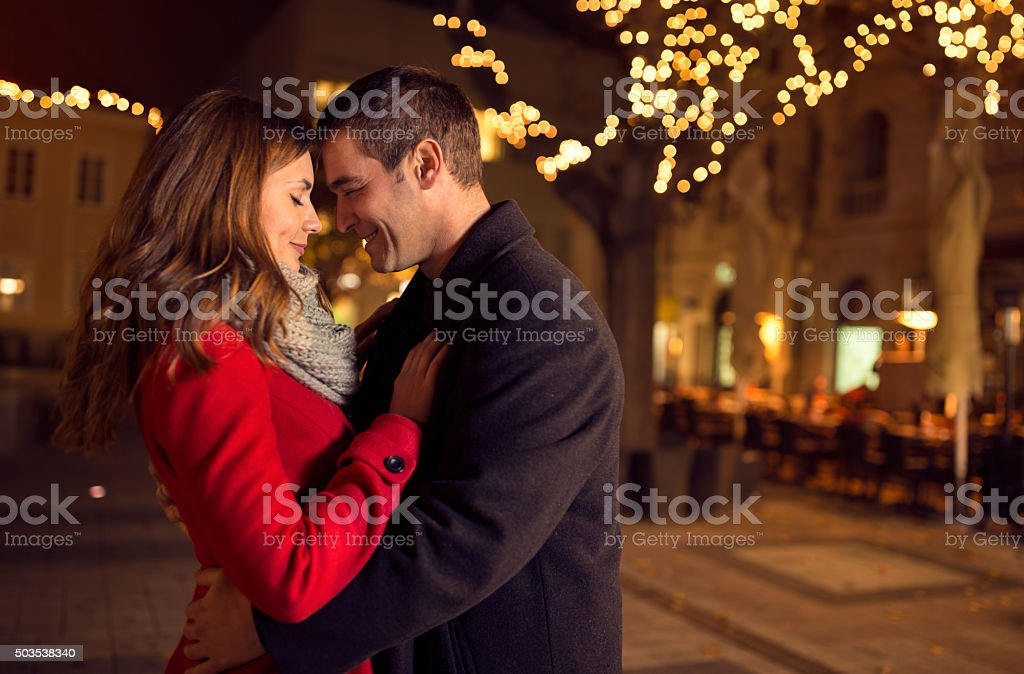 Young happy attractive amorous couple embracing outdoors stock photo