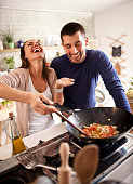 young happy attractive couple at home kitchen tasting