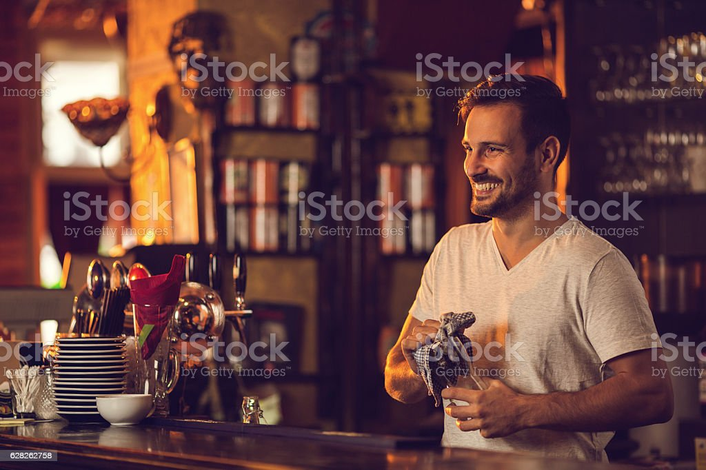 Young happy bartender cleaning drinking glass after work. stock photo