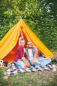 Young happy beautiful couple sitting at the tent