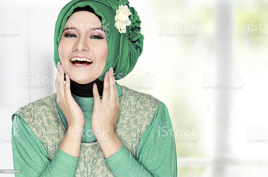 Young happy beautiful muslim woman with green costume wearing hi stock photo