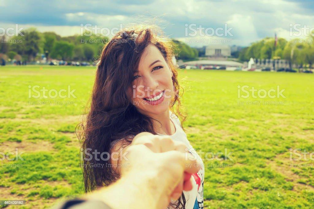 Young happy beautiful woman leading man stock photo