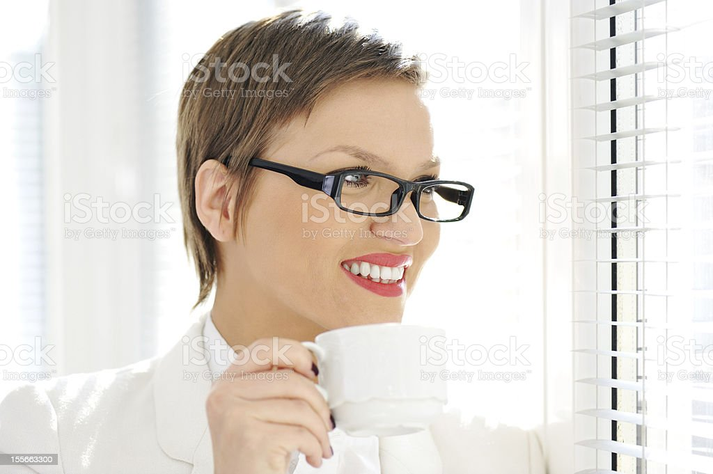 Young happy business woman drinking coffee at office royalty-free stock photo