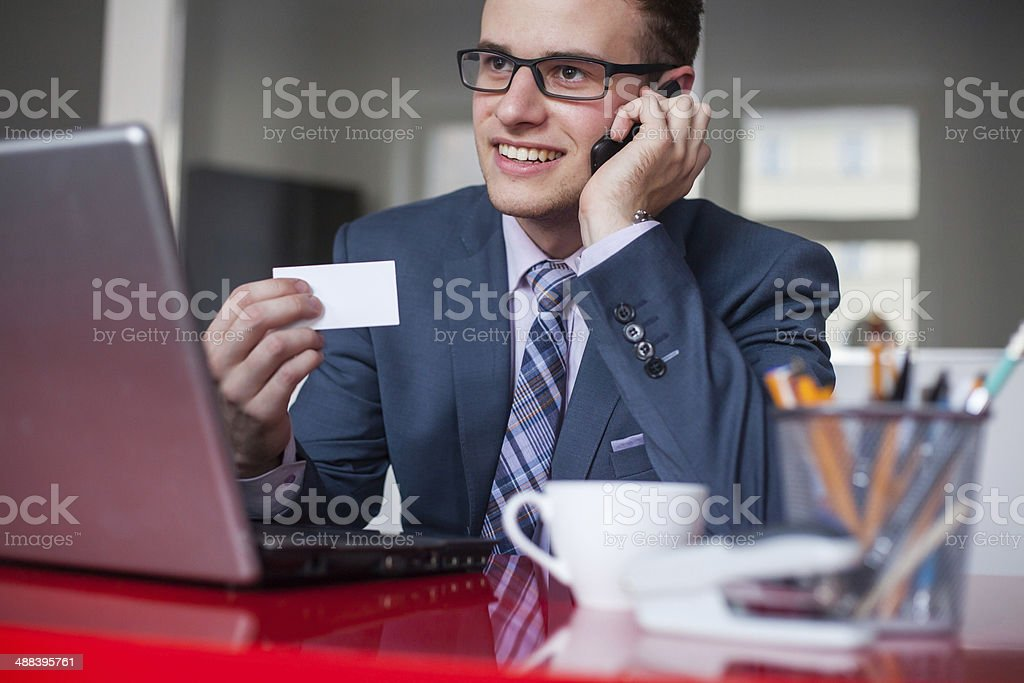 Young happy businessman holding mobile phone and white business card. stock photo