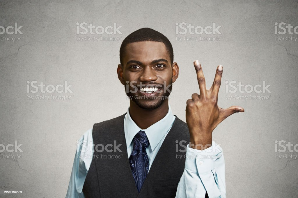 young happy, confident, handsome business man giving a three times fingers sign stock photo