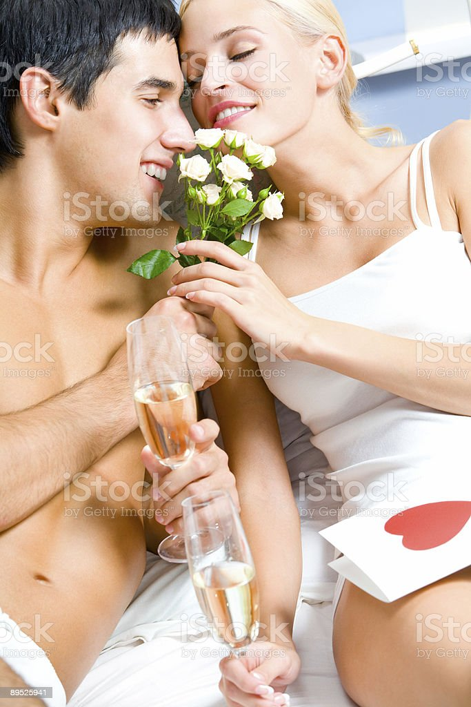Young happy couple celebrating with champagne at bedroom royalty-free stock photo