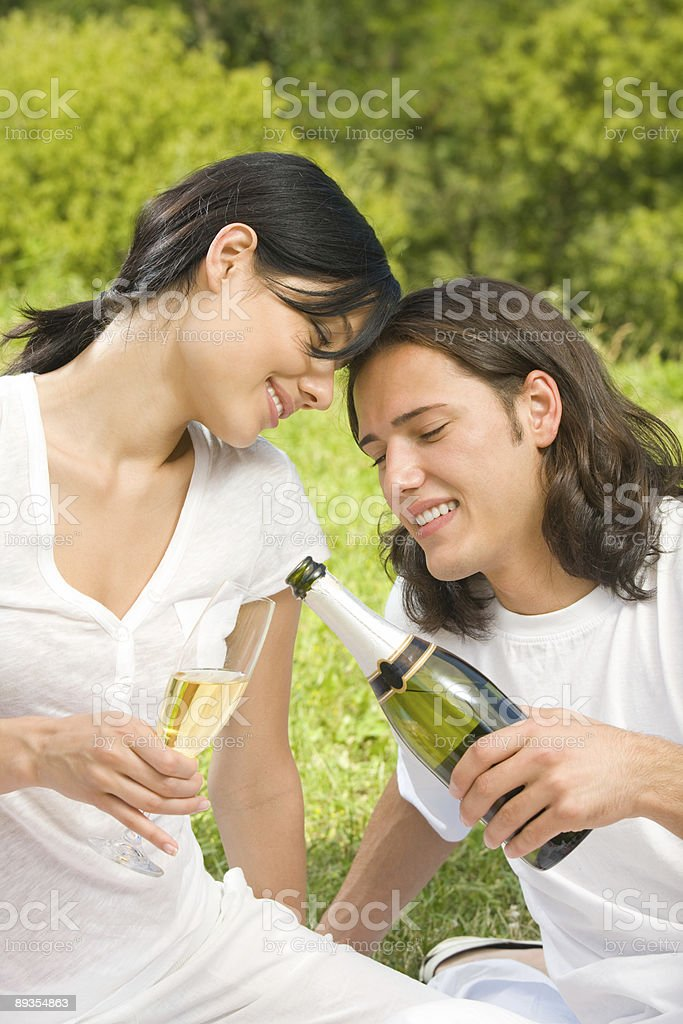 Young happy couple celebrating with champagne at picnic royalty-free stock photo