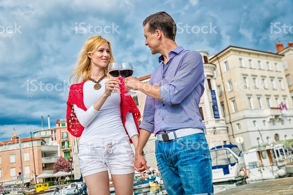 Young happy couple celebrating with red wine stock photo