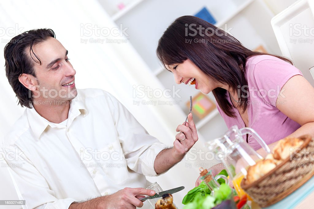 Young happy couple eating vegetables for dinner royalty-free stock photo