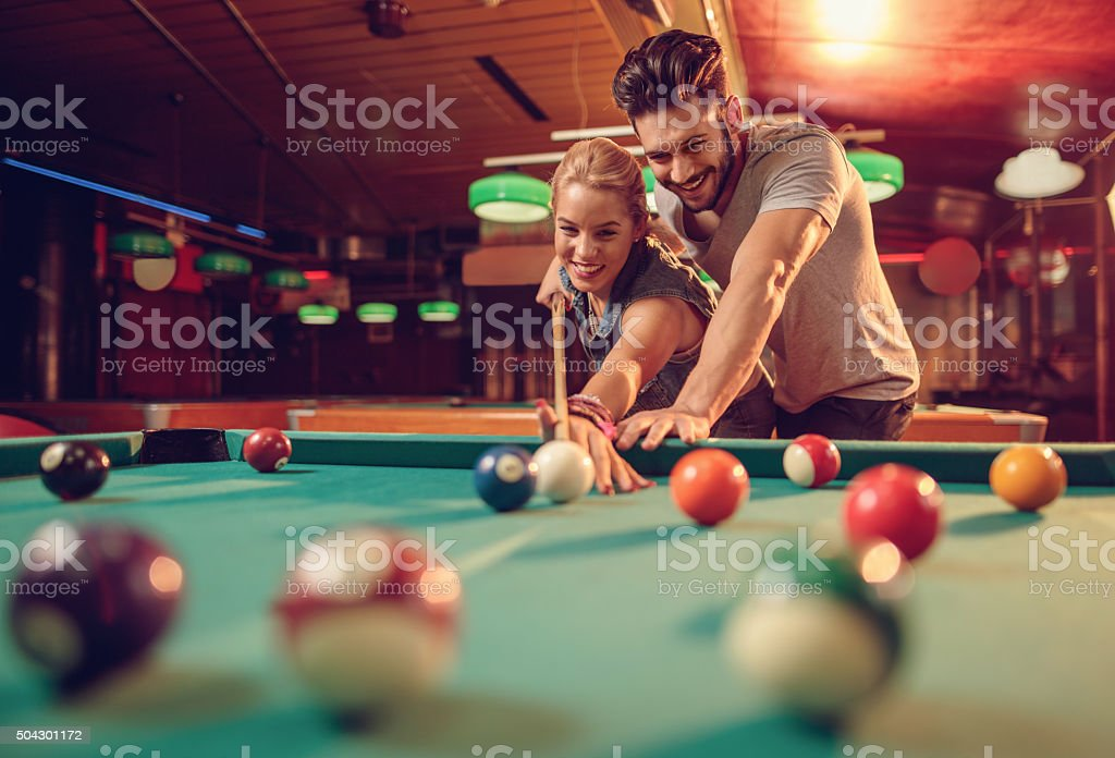 Young happy couple enjoying in a billiard game together. stock photo
