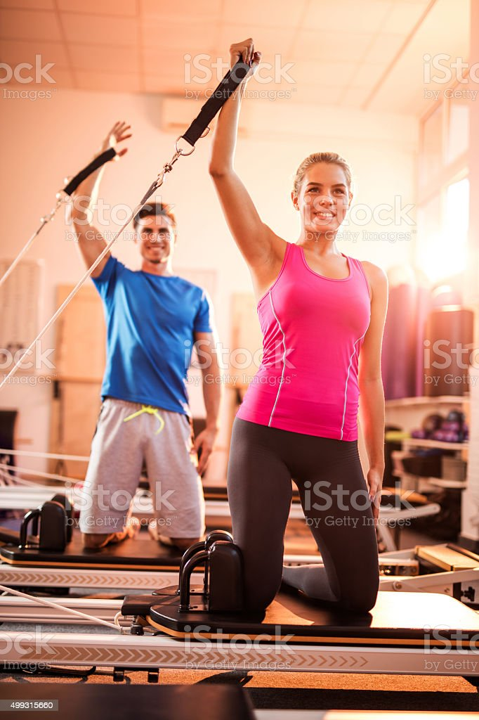 Young happy couple exercising on Pilates machine in health club. stock photo