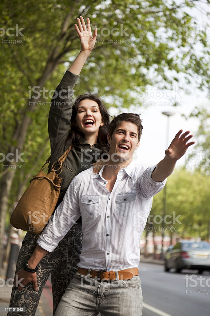 Young Happy Couple Hailing A Taxi In London royalty-free stock photo