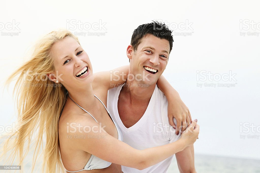 Young happy couple having fun on the beach royalty-free stock photo