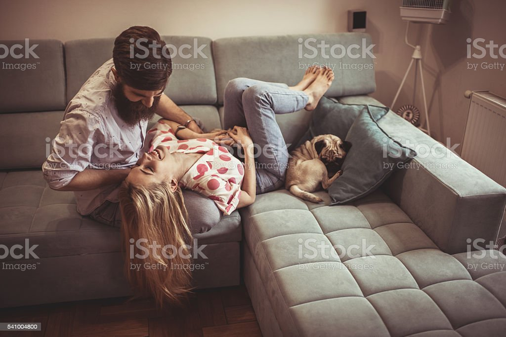 Young happy couple having fun together on sofa at home. stock photo