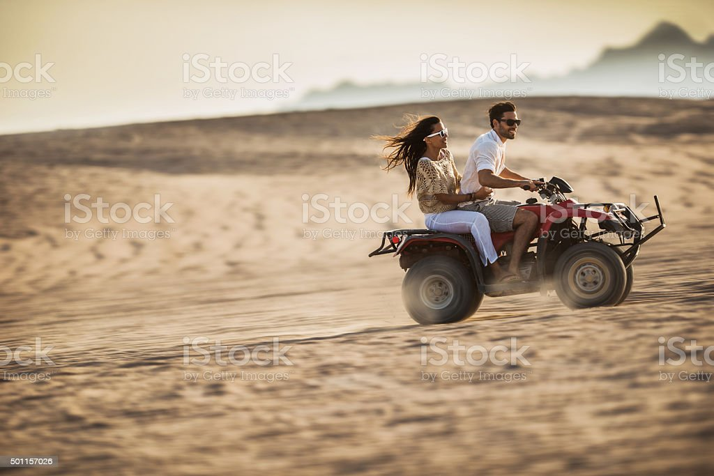 Young happy couple having fun while driving on quad bike. stock photo