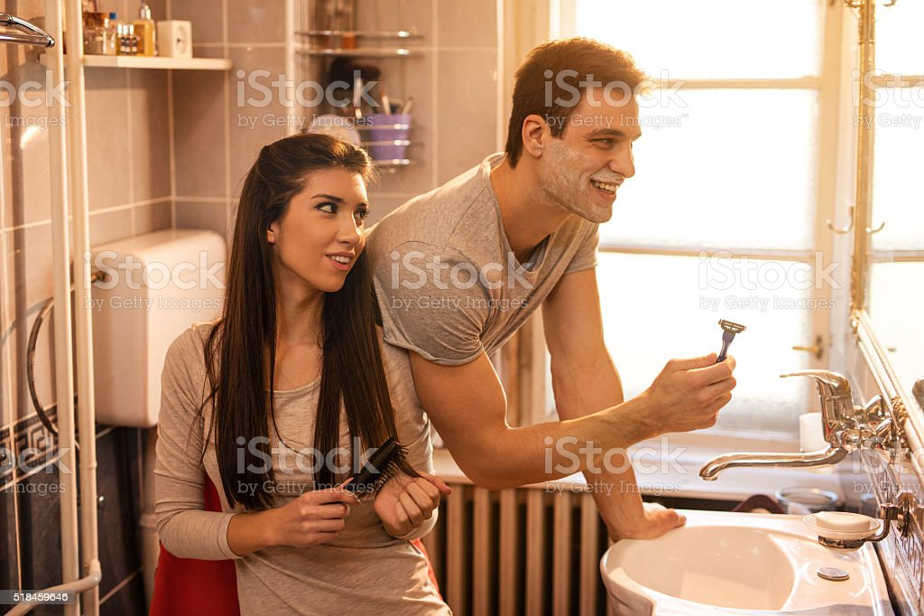 Young happy couple in the bathroom in the morning. stock photo