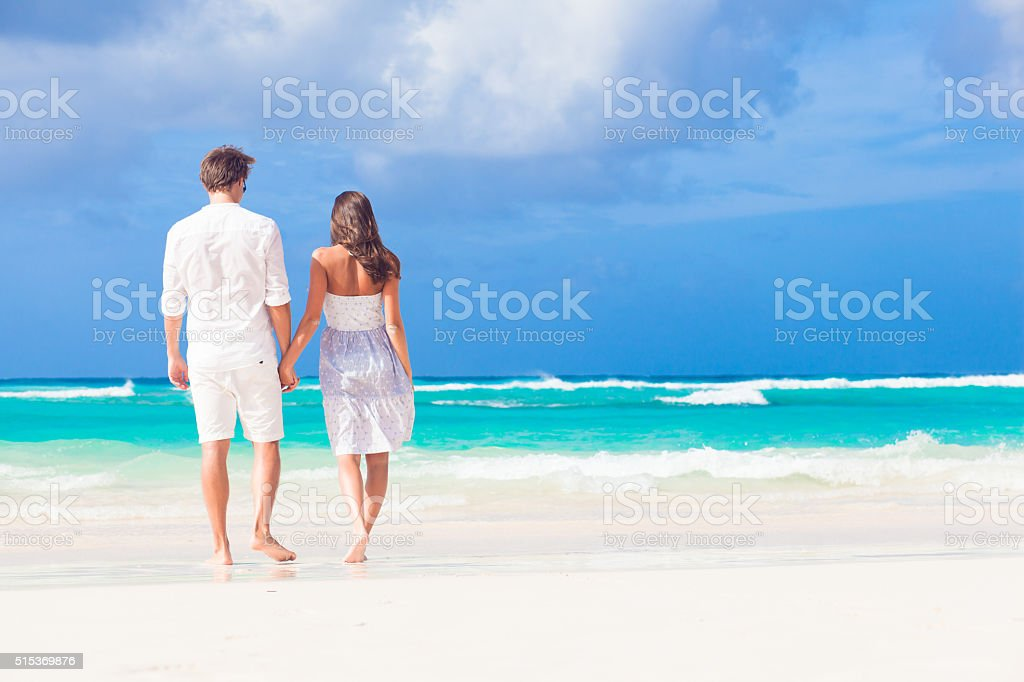 young happy couple in white at tropical beach. honeymoon stock photo