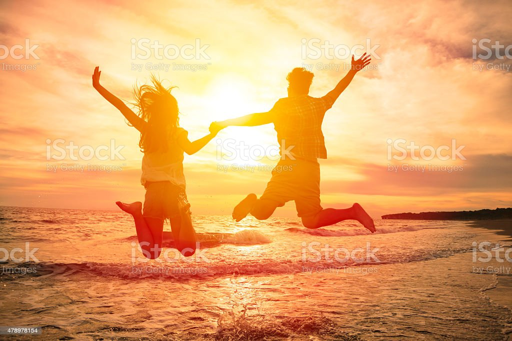 young happy couple jumping on beach stock photo