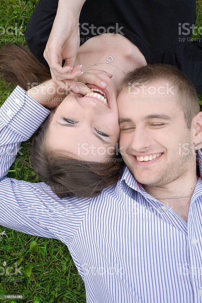 Young happy couple laying on grass royalty-free stock photo
