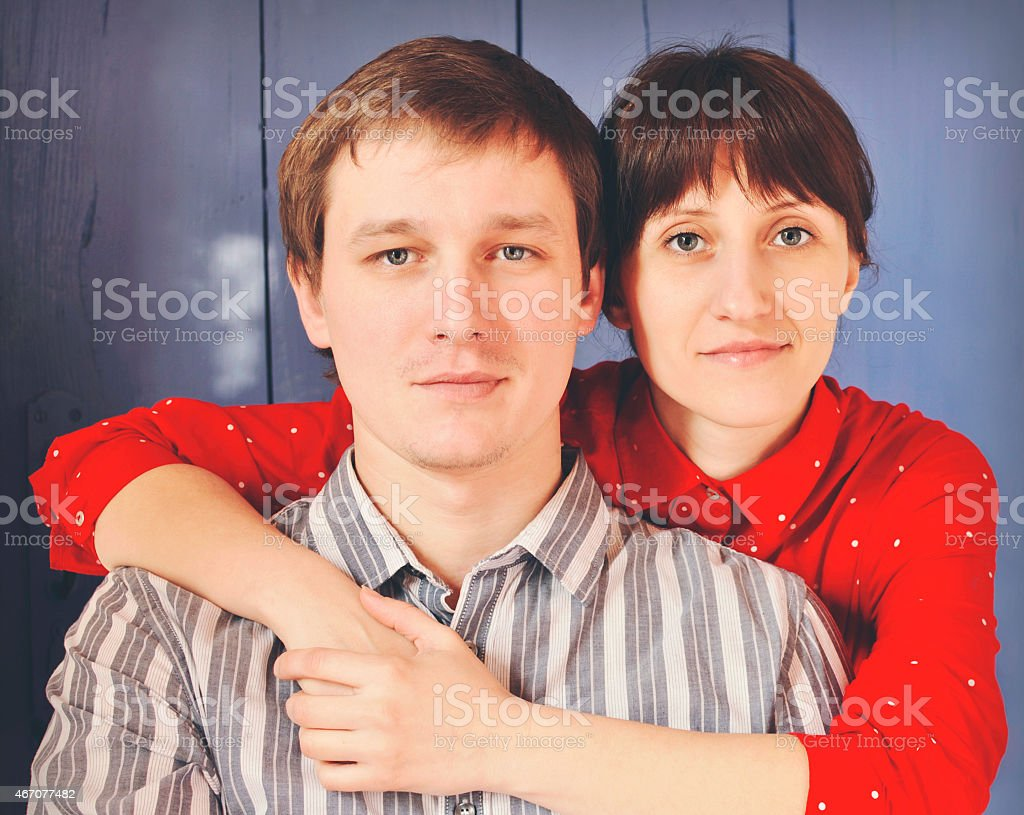 Young happy couple on the backgroound of blue wooden door stock photo