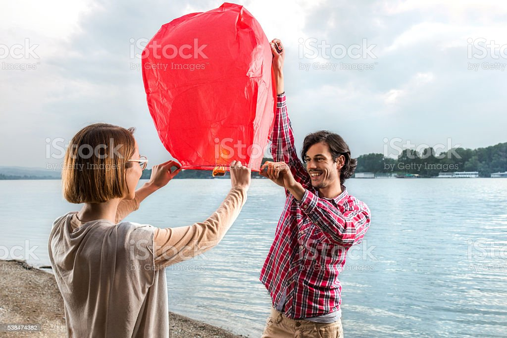 Young happy couple on the beach releasing sky lantern. stock photo