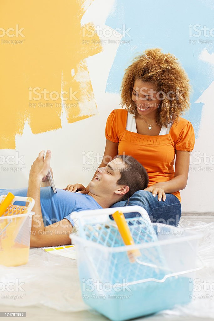 Young Happy Couple Painting the wall and have break. royalty-free stock photo