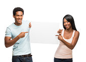 Young happy couple pointing at white sign