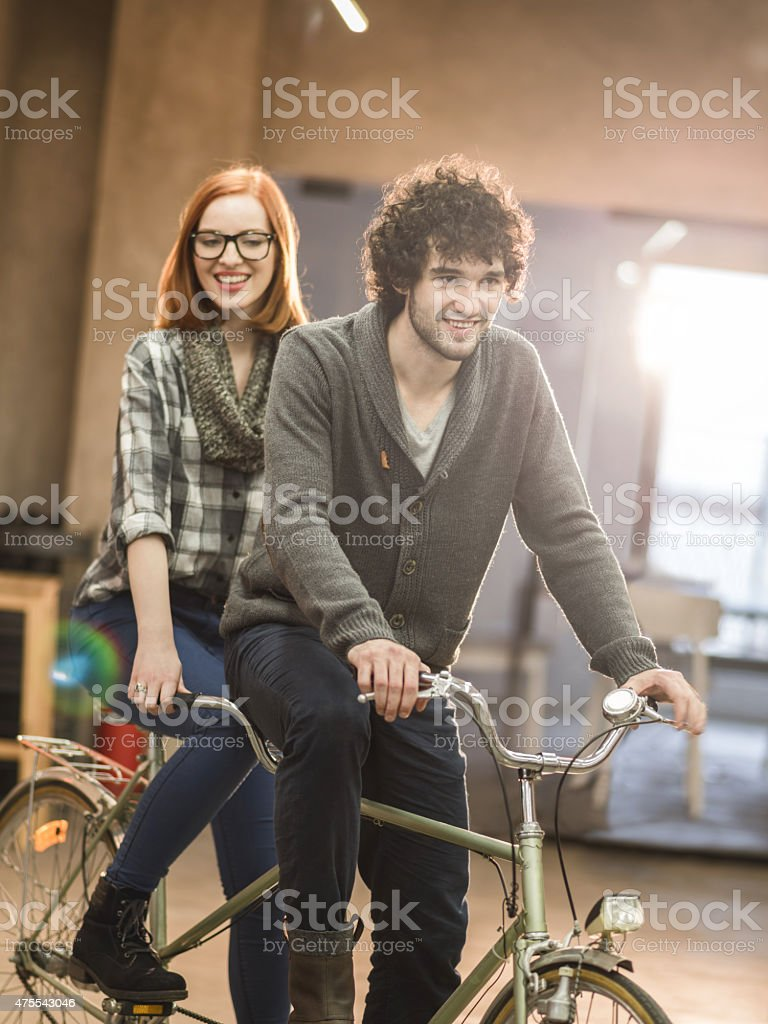 Young happy couple riding a tandem bike indoors. stock photo