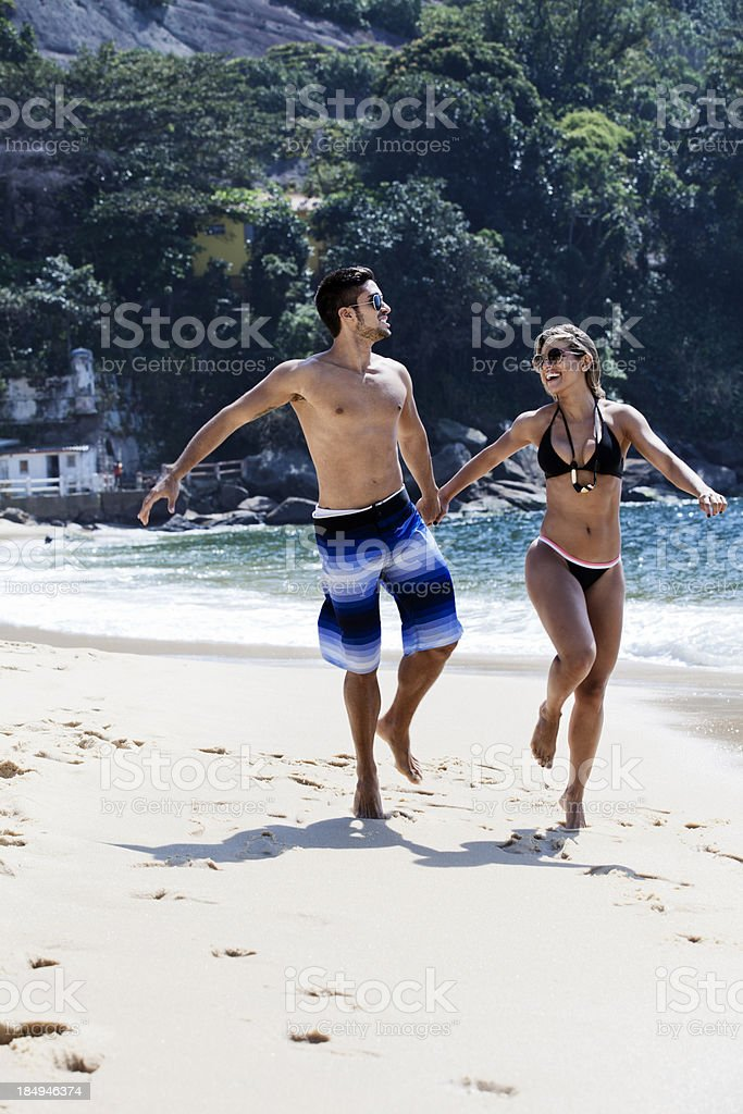 Young happy couple running on the beach royalty-free stock photo