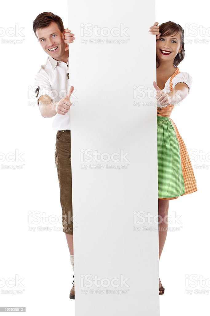 Young happy couple stand behind billboard and show thumbs up royalty-free stock photo